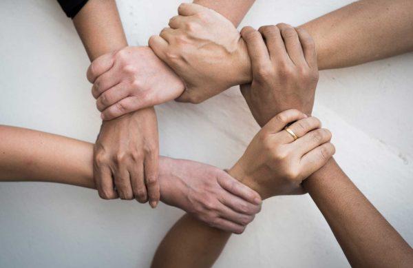 people-united-hands-together-teamwork-scaled